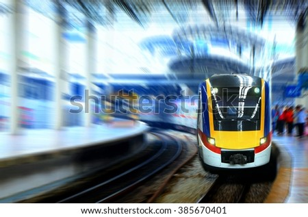 Fast moving train leaving station platform  - stock photo