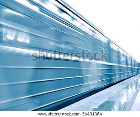 Fast moving train on underground platform - stock photo