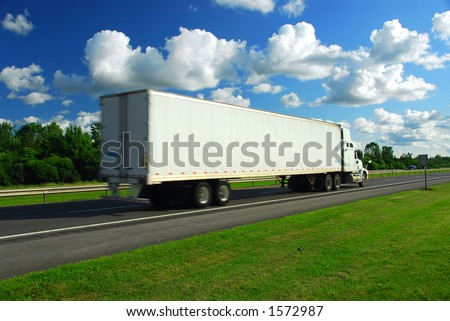 Fast moving truck with white container on highway, blurred because of motion - stock photo
