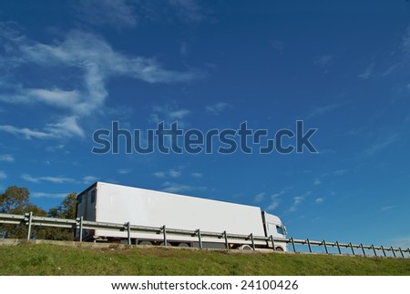 Fast moving truck with white container on highway, blurred because of motion