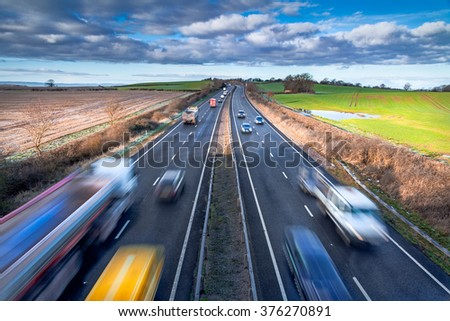 Fast moving Vehicles on Busy Motorway at the Morning - stock photo