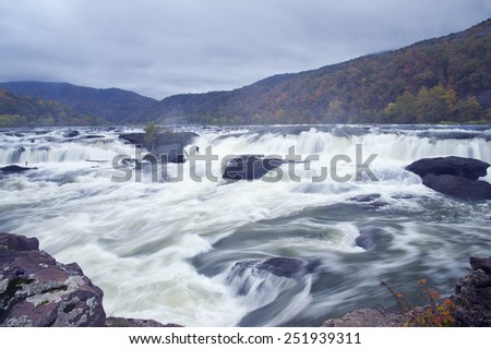 Fast moving waterfall on a cloudy fall day - stock photo