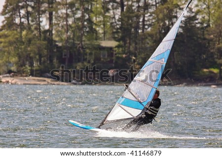 Fast moving windsurfer on the water - stock photo