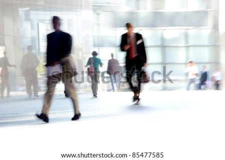 Fast Paced Business World with Blurred Motion. People walking. All exposed faces are motion blurred. - stock photo