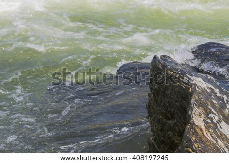 Fast river waves background. Rock and waves close up. fast rapid current. Danger zone. Stream flowing fast over rocks - stock photo