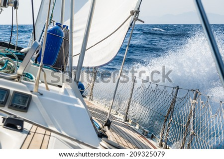 Fast sailing cruising yacht at heeling with splash - stock photo