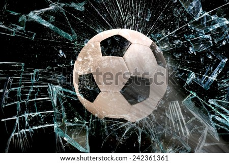 Fast Soccer ball through broken glass. - stock photo
