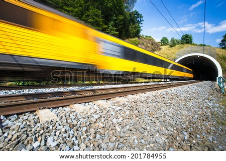Fast train passing through a tunnel on a lovely summer day (motion blurred image) - stock photo