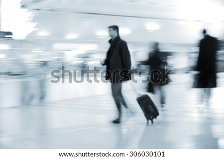 Fast walking businessmen in an airport - stock photo