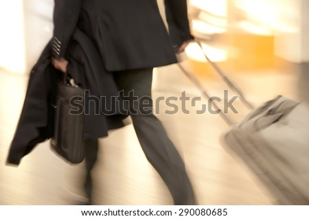Fast walking businessmen in an airport building