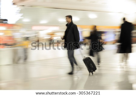 Fast walking businessmen in an airport. Business or travel background. - stock photo