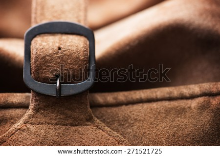 Fastened buckle. Buckle section of a leather bag or case. Extremely shallow depth of focus. Focus is on buckle pin. - stock photo