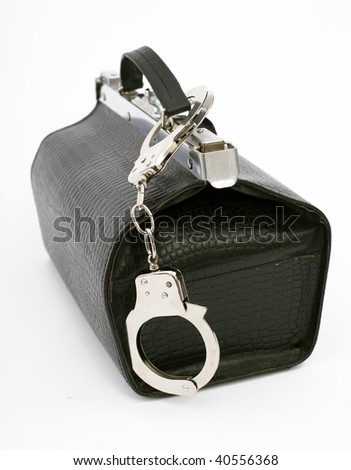 fastened handcuffs pinned to standing, black leather bag from handle