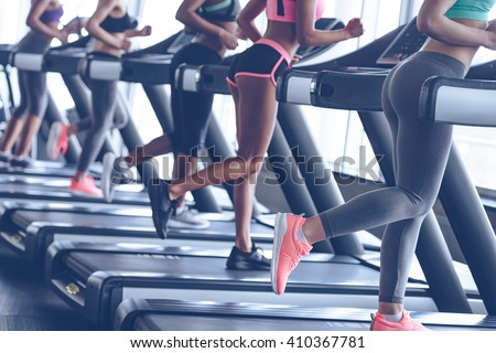 Faster and stronger. Side view part of young women with perfect buttocks running on treadmill at gym