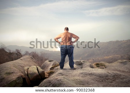 Fat bare-chested man in the mountains - stock photo