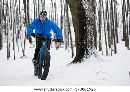 Fat biker riding his bicycle in the snow during Canadian winter - stock photo