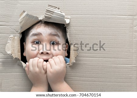 fat boy looking through hole on cardboard with funny shocked face expression halloween concept