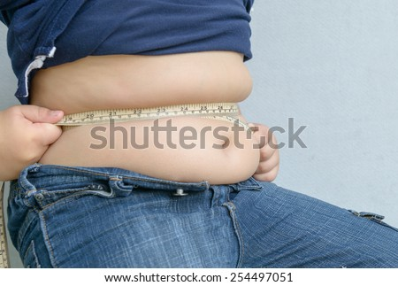 Fat boy measuring his belly with measurement tape - stock photo
