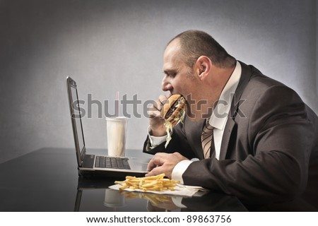 Fat businessman eating junk food while working - stock photo