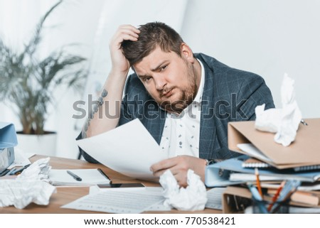 fat businessman in suit doing paperwork in office