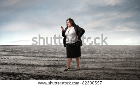 Fat businesswoman standing alone in a field - stock photo