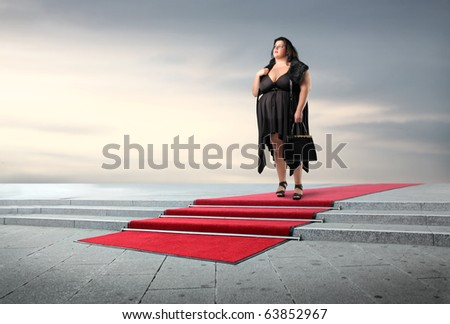 Fat elegant woman standing on a red carpet - stock photo