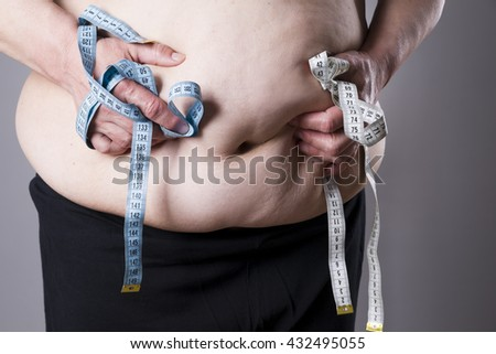 Fat female body with measuring tape on gray background - stock photo