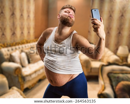 Fat glamour man with beard takes selfie in his bedroom - stock photo