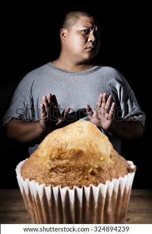 Fat guy refusing junk food. - stock photo