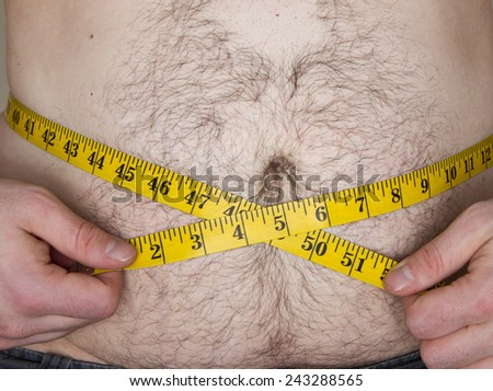 Fat guy with a tape measure over his belly trying to measure his weight - stock photo