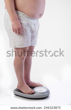 Fat male on the weight scale - stock photo