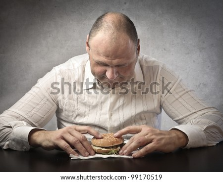 Fat man about to eat a hamburger - stock photo