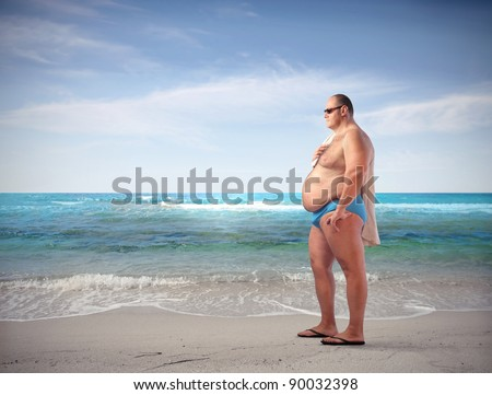 Fat man at the seaside - stock photo