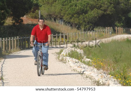 Fat man cycling on the countryside making exercise - stock photo