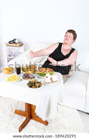 Fat man  do not want to eat a lot of unhealthy food, on home interior background   - stock photo