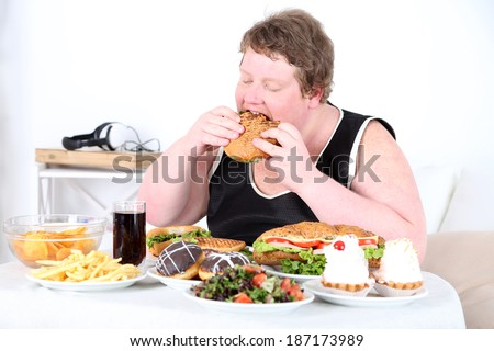 Fat man eating a lot of unhealthy food, on home interior background   - stock photo