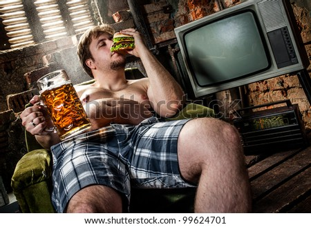 fat man eating hamburger seated on armchair - stock photo