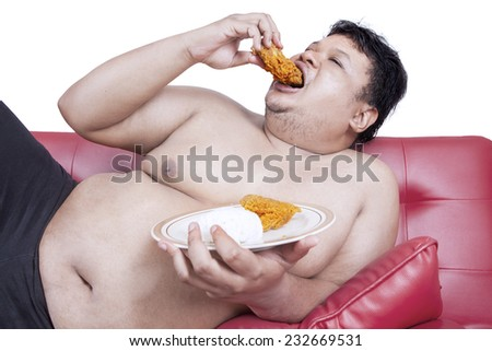 Fat man eats fast food while sitting on sofa at home - stock photo