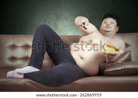 Fat man eats fast food while watching tv at home - stock photo
