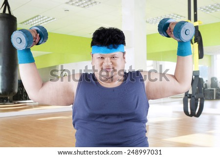 Fat man exercise in fitness center by lifting two dumbbells - stock photo