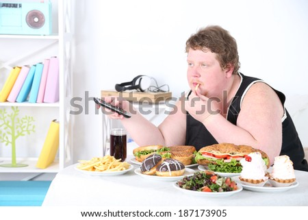 Fat man has a big lunch and watching TV, on home interior background   - stock photo