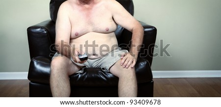 Fat man holding a remote while watching tv - stock photo