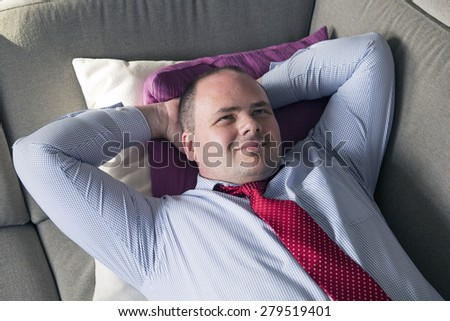 fat man in shirt and tie lying on couch and smiles - stock photo