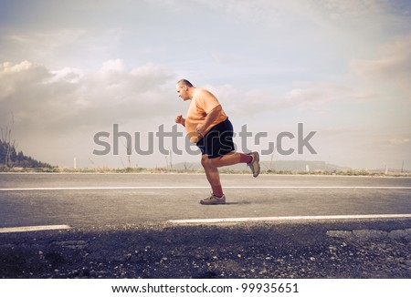 Fat man jogging on a country road - stock photo