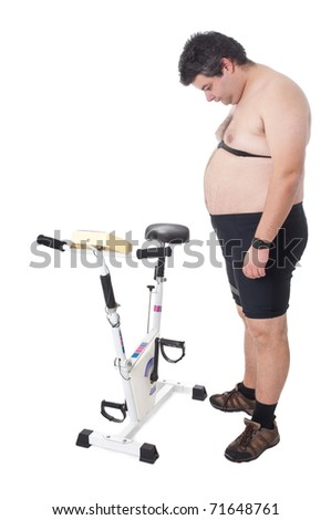 Fat man looking to a static bicycle - stock photo