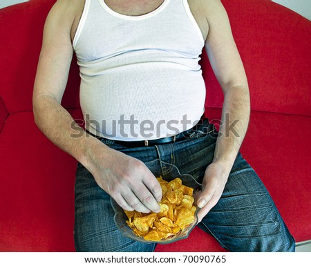 fat man on red couch eating potato chips.