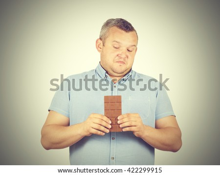 fat man refuses to chocolate. Diet, overweight, healthy food isolated on background. - stock photo