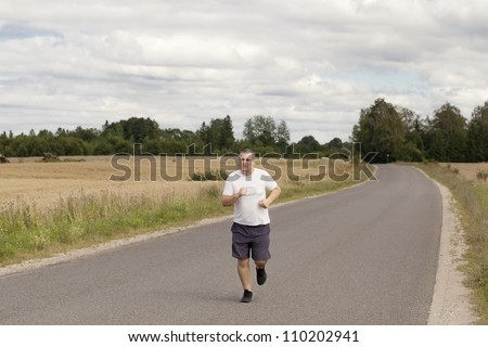 Fat man running on a rural road - stock photo