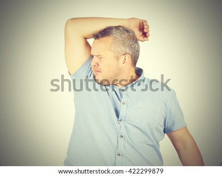 Fat man, smelling sniffing his armpit, something stinks bad, foul odor isolated on background.       - stock photo