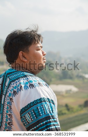 Fat man watching the beautiful pensive dreamy magical mountain landscape. Time for reflection and refresh yourself. Enjoy a holiday - stock photo